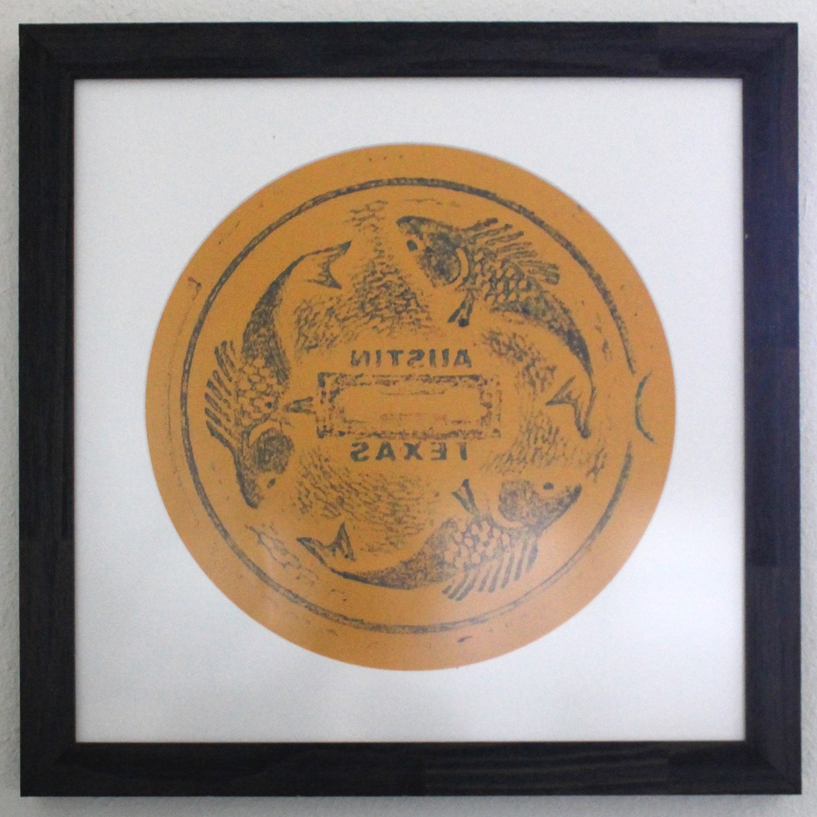 A blue and green rubbing on orange paper, in a circular mat, in a square dark purple frame. The rubbing design features three stylized fish chasing each other around a circle, with the words AUSTIN TEXAS mirror-reversed at the center.