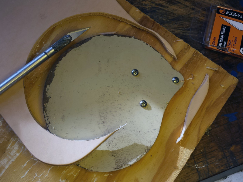 2. Trace around the perimeter of the fan blade with a sharp hobby knife, cutting through the leather as you go. It will likely take a couple of passes.