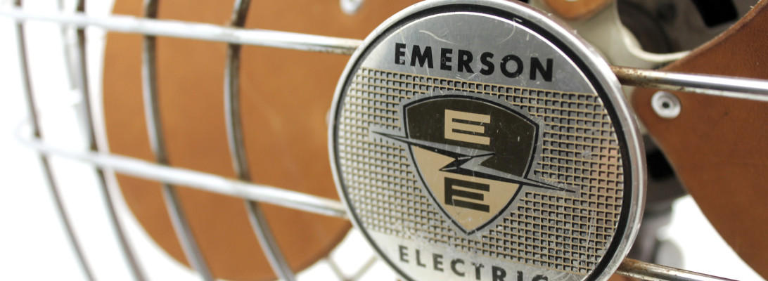A close up shot of the EMERSON ELECTRIC logo medallion on the front of a wire fan cage, with the replaced leather blades out of focus behind.