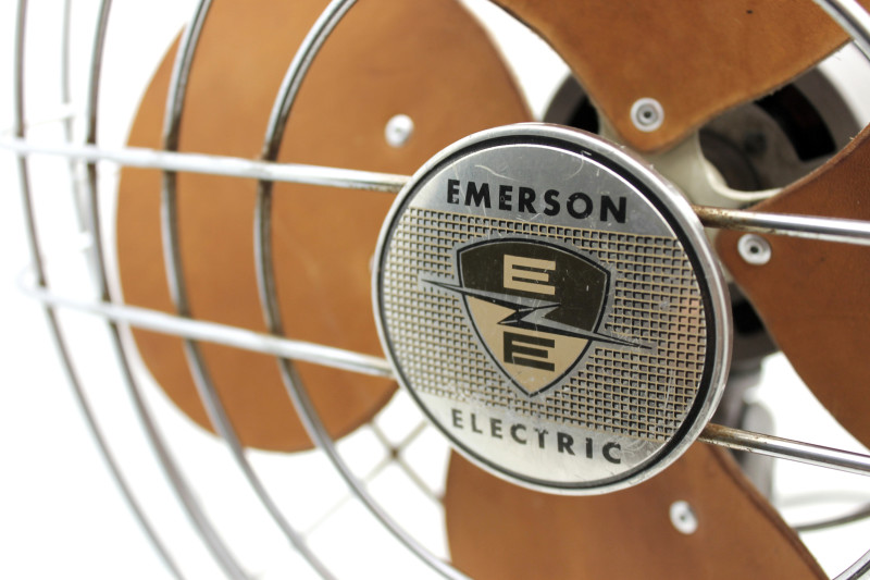 A close shot of the EMERSON ELECTRIC logo medallion on the front of a wire fan cage, with the replaced leather blades out of focus behind.
