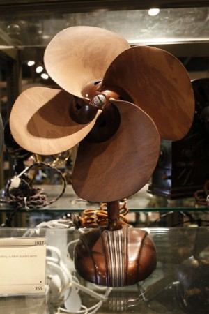 A desk fan, in front view, with no cage, and large free-spinning blades made of brown leather. The base is also brown and has attractive Art Deco styling elements.